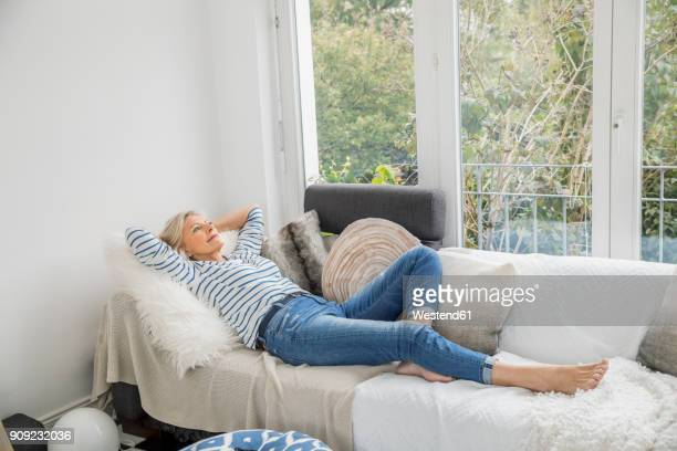 smiling senior woman relaxing on couch in the living room - sdraiato foto e immagini stock
