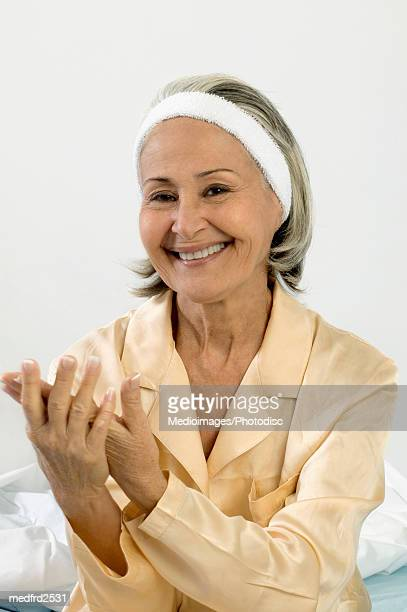 Smiling senior woman rubbing hands together, close-up