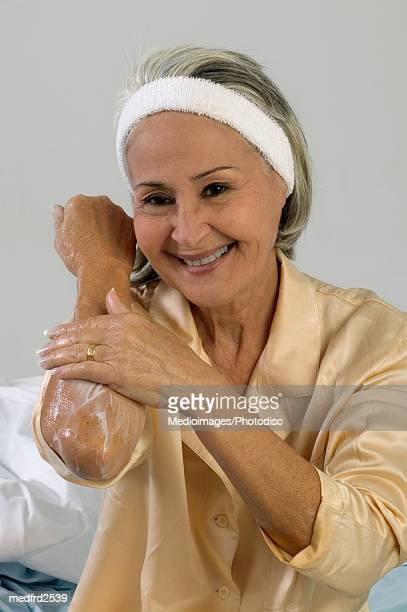 Smiling senior woman rubbing lotion on arm, close-up