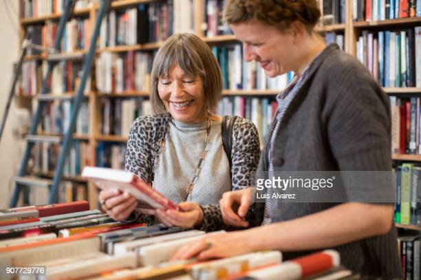 Smiling senior woman showing book to young female