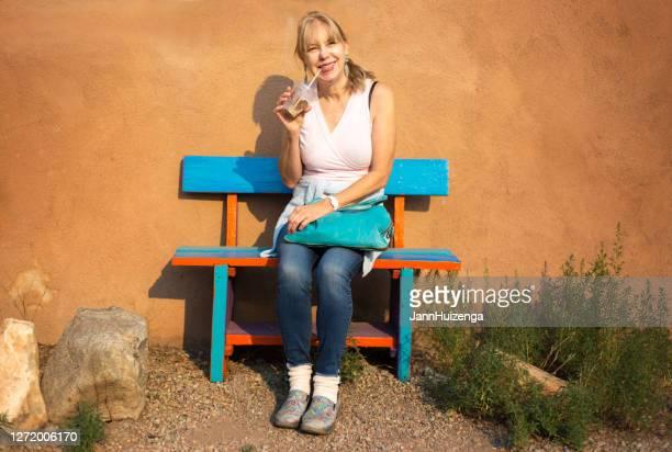 sitting et boire de femme aîné de sourire - sac à main rouge photos et images de collection