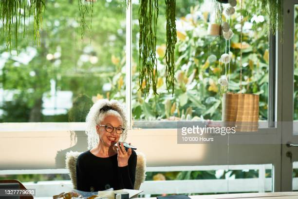 smiling senior woman sitting holding speaker phone - greater london stock pictures, royalty-free photos & images