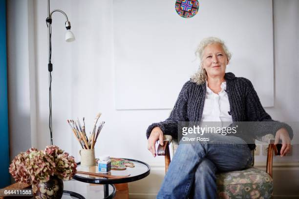 Smiling senior woman sitting in armchair at home