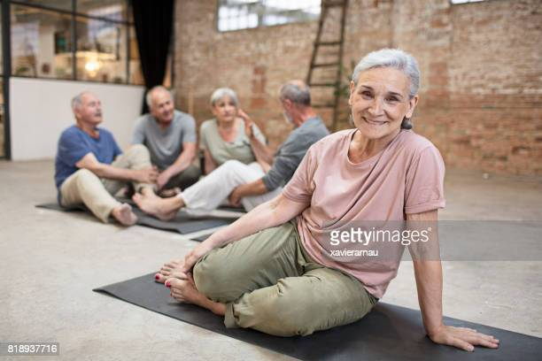 Smiling senior woman sitting in yoga class