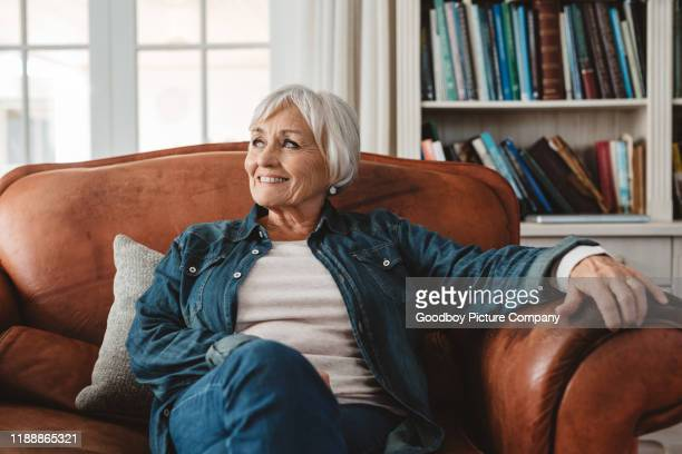 smiling senior woman sitting on her sofa at home - chair stock pictures, royalty-free photos & images