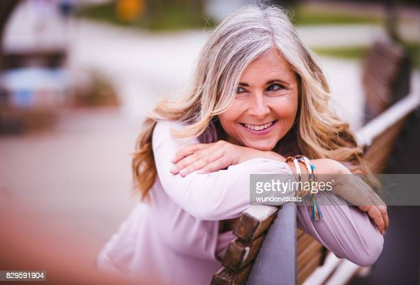 Smiling senior woman sitting on park bench in spring