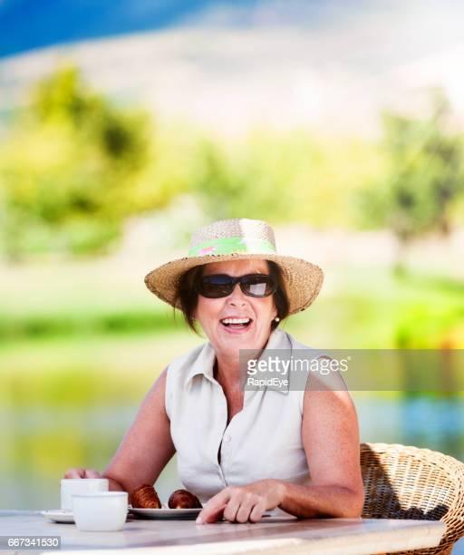 Smiling senior woman sitting over coffee beside a beautiful lake
