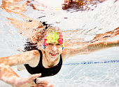 Smiling senior woman swimming in pool