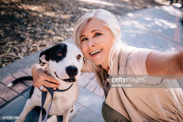 smiling senior woman taking selfies with pet dog in park - dog walker stock photos and pictures
