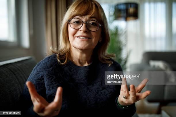 sonriente mujer mayor hablando en videollamada en casa - hablar fotografías e imágenes de stock