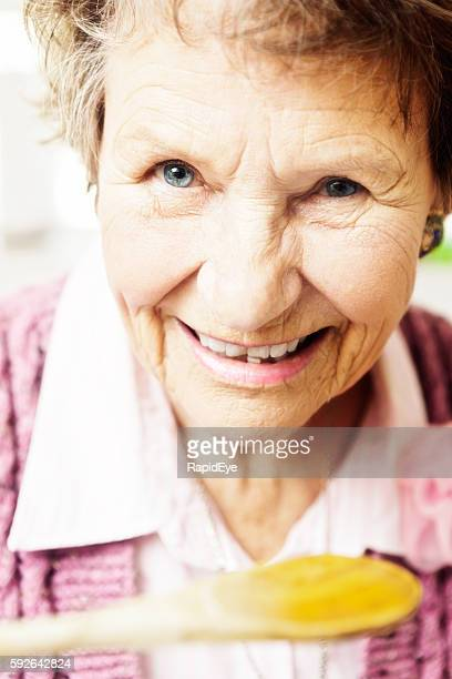 Smiling senior woman tasting something from a wooden spoon