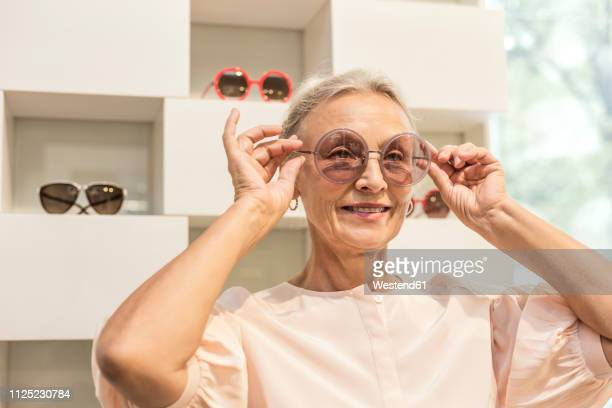 smiling senior woman trying on sunglasses in a boutique - óculos escuros acessório ocular - fotografias e filmes do acervo