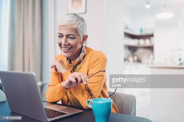 smiling senior woman using laptop at home - white hair stock pictures, royalty-free photos & images