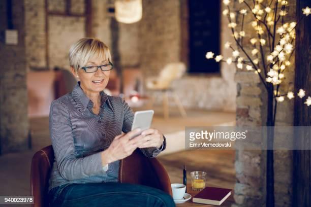 Smiling senior woman using mobile phone in living room