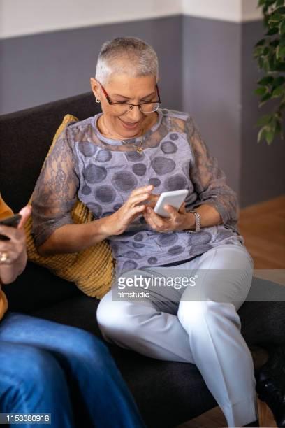 lachende senior vrouw met behulp van slimme telefoon thuis - alleen één seniore vrouw stockfoto's en -beelden