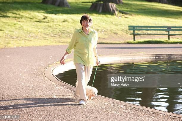Smiling senior woman walking her dog around a lake