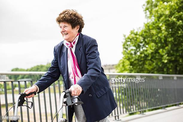 Smiling senior woman walking with wheeled walker