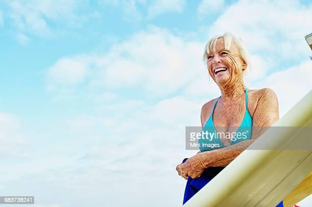 smiling senior woman wearing a bikini and wetsuit standing net to a surfboard. - eine seniorin allein stock-fotos und bilder