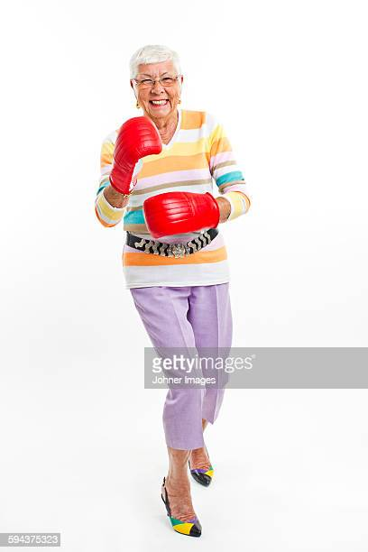 smiling senior woman wearing boxing gloves - funny boxing stock photos and pictures