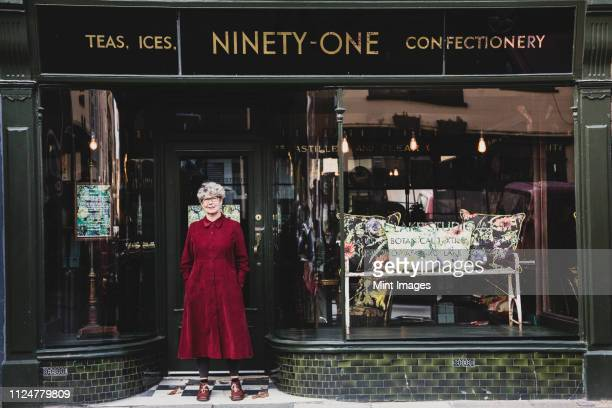 smiling senior woman wearing glasses and red dress standing front of interior design store, looking at camera. - shop window stock pictures, royalty-free photos & images