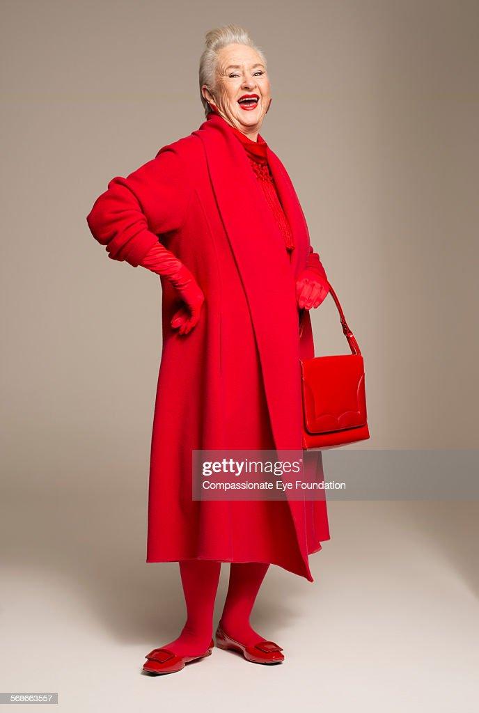 Smiling senior woman wearing red coat : Stock Photo