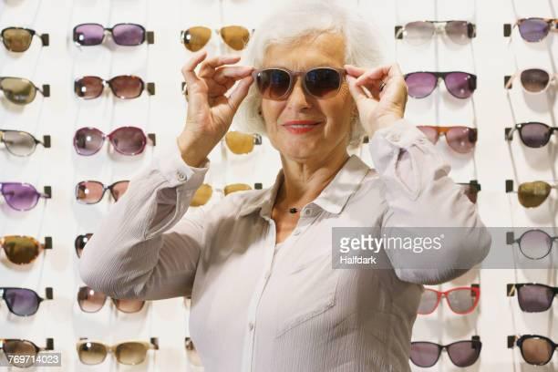 smiling senior woman wearing sunglasses while standing at store - eine seniorin allein stock-fotos und bilder