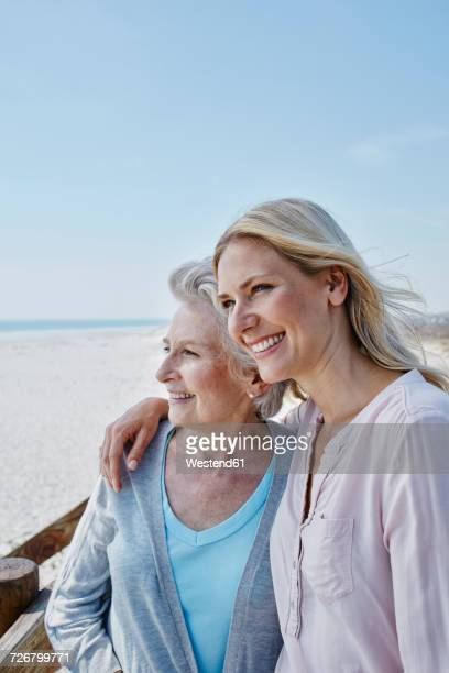 Smiling senior woman with adult daughter on the beach