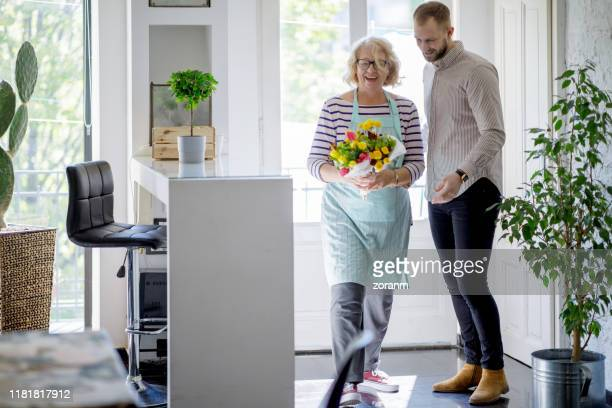 smiling senior woman with bunch of flowers received from young man - receiving stock pictures, royalty-free photos & images