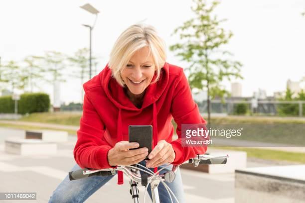 smiling senior woman with city bike using cell phone - nederzettingen stockfoto's en -beelden