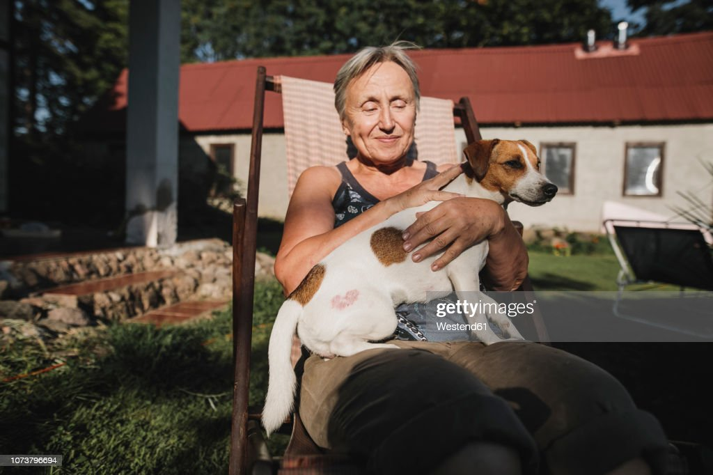 Smiling senior woman with dog on deckchair in garden : Stock-Foto