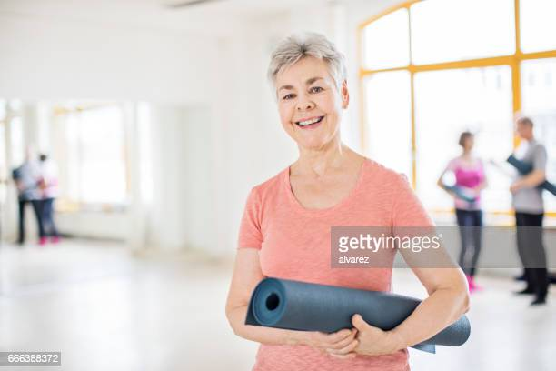 Smiling senior woman with exercise mat in class
