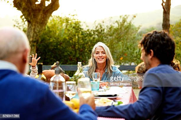 Smiling senior woman with family at meal table
