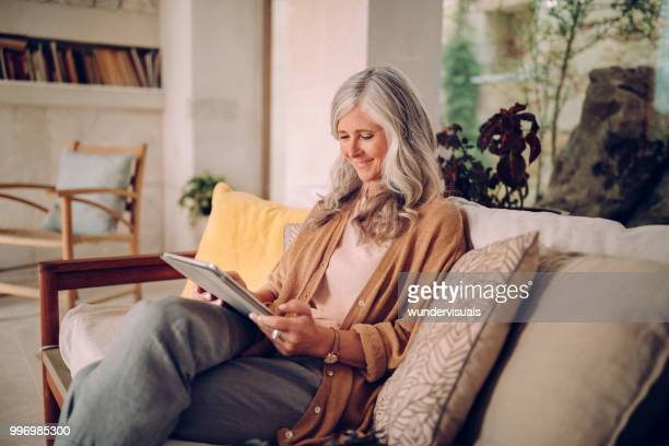 smiling senior woman with gray hair using tablet at home - mature women stock pictures, royalty-free photos & images