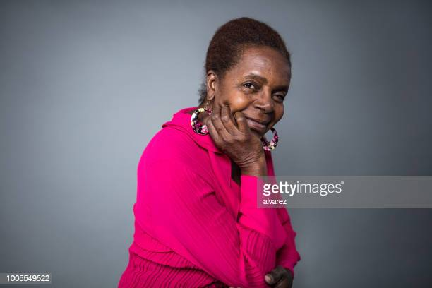 Smiling senior woman with hand on chin