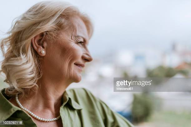 Smiling senior woman with hearing aid outdoors