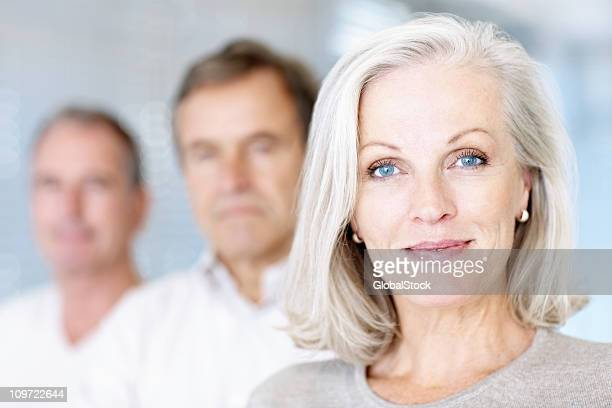 smiling senior woman with men at the background - blue eyes stock pictures, royalty-free photos & images