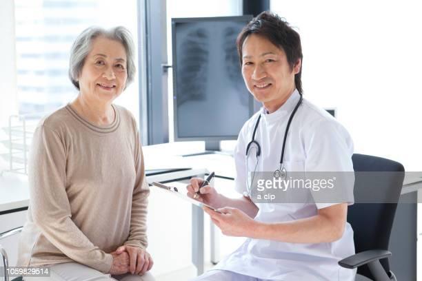 smiling senior women and male doctors - opslagmedia voor analoge audio stockfoto's en -beelden