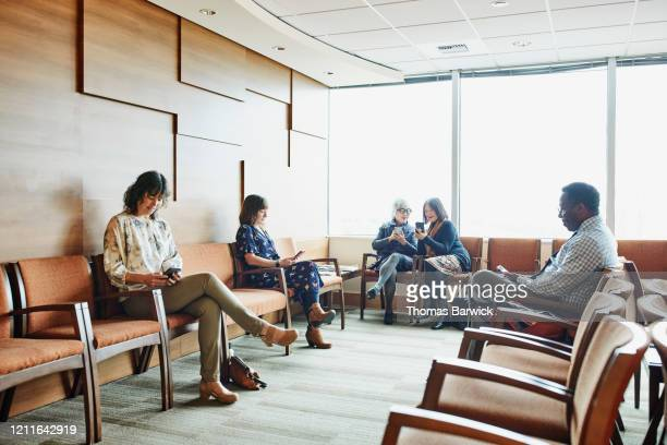 smiling senior women sharing photos on smart phones while sitting in medical office waiting room - patience stock pictures, royalty-free photos & images