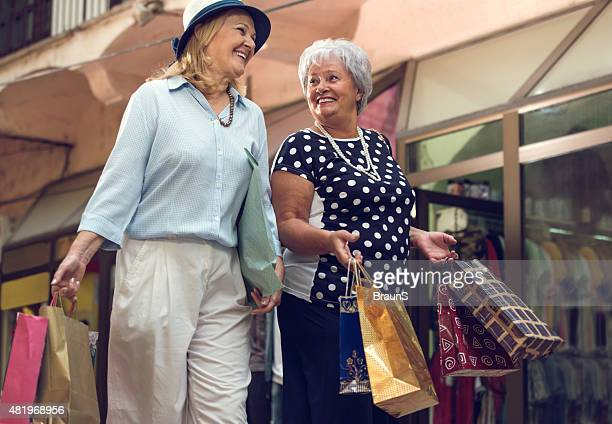 Smiling senior women talking to each other in shopping.