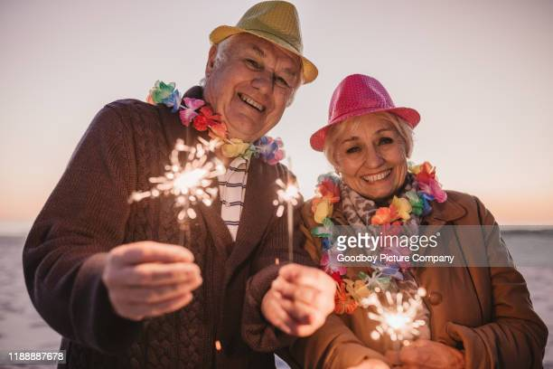 smiling seniors celebrating new year's with sparklers at the beach - 70 year old man stock pictures, royalty-free photos & images