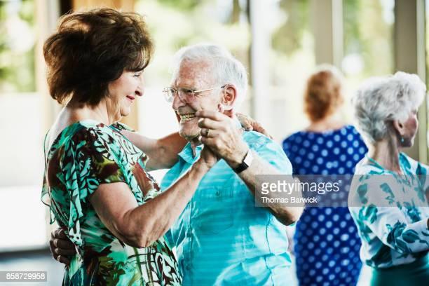 Smiling seniors dancing together in community center
