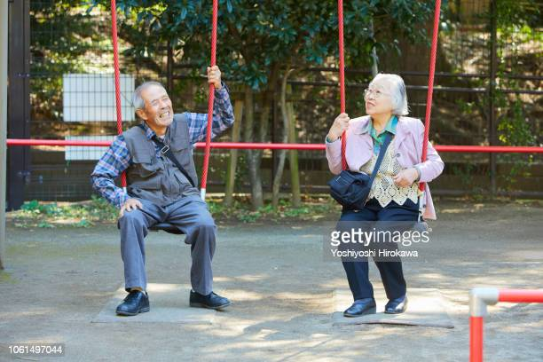 smiling seniors who sitting on a swing while walk in the park - 日本の神社 ストックフォトと画像