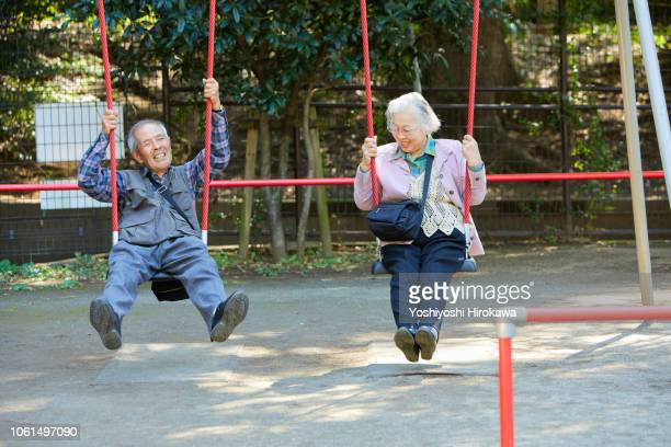 smiling seniors who sitting on a swing while walk in the park - snapping the ball stock pictures, royalty-free photos & images