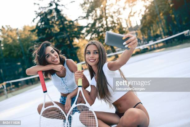 smiling sensual females sitting on tennis court and taking selfie - giochi erotici foto e immagini stock
