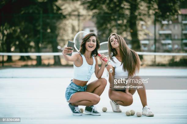 Smiling Sensual Females Sitting on Tennis Court and Taking Selfie