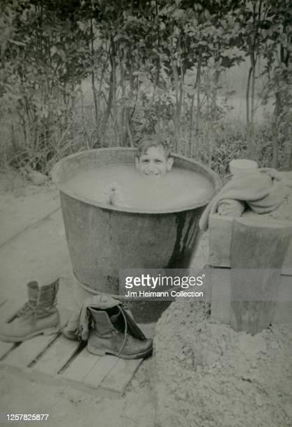 Smiling serviceman takes a bath in giant outdoor tub, circa 1952.