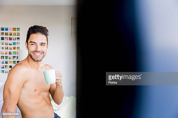 Smiling shirtless young man having coffee at home