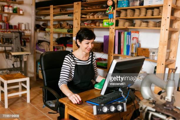 Smiling shoemaker using computer in her workshop