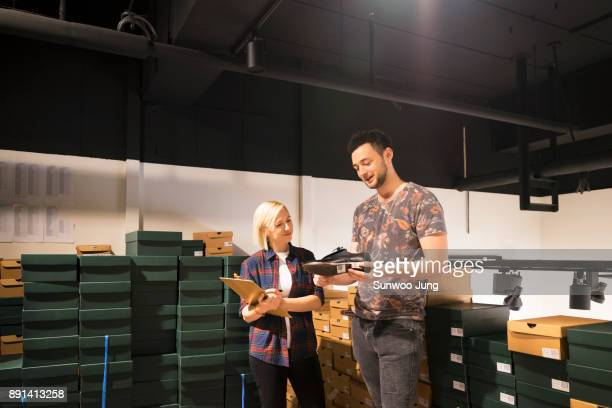 Smiling shop owner in discussion with clerk in product storage