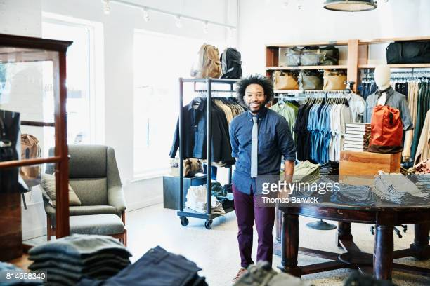 Smiling shop owner standing in mens clothing boutique